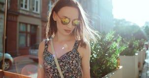 Retrato de las gafas de sol que llevan de la muchacha hermosa que se colocan en una calle de la ciudad Foto de archivo libre de regalías