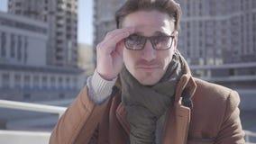 Retrato de las gafas de sol que llevan de un hombre elegante hermoso que se sientan contra un fondo de la arquitectura urbana almacen de video