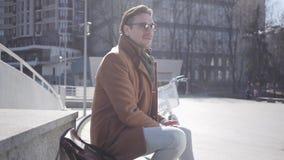 Retrato de las gafas de sol que llevan de un hombre elegante ttractive que se sientan contra un fondo de la arquitectura urbana metrajes