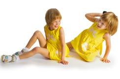 Retrato de las hermanas gemelas alegres que abrazan y que sonríen en la leva Fotografía de archivo libre de regalías