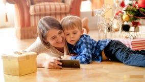 Retrato de las historietas de observación del niño pequeño en el teléfono móvil con la madre debajo del árbol de navidad imágenes de archivo libres de regalías