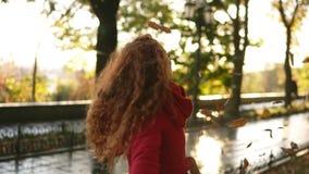 Retrato de las hojas que lanzan de una mujer principal roja feliz alrededor en un día de los otoños Hojas de otoño que caen en mu metrajes