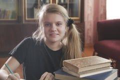 Retrato de las lecciones que hacen adolescentes de una muchacha en casa Imagen de archivo libre de regalías