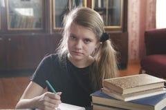 Retrato de las lecciones que hacen adolescentes de una muchacha en casa Foto de archivo