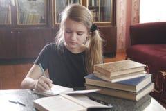 Retrato de las lecciones que hacen adolescentes de una muchacha en casa Fotos de archivo libres de regalías