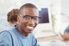 Retrato de las lentes que llevan del hombre feliz mientras que se sienta en el escritorio Fotos de archivo