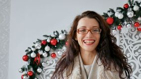 Retrato de las lentes que llevan de una muchacha morena feliz y del suéter caliente en el fondo de la decoración de la Navidad Mu metrajes