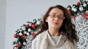 Retrato de las lentes que llevan de una muchacha morena feliz y del suéter caliente en el fondo de la decoración de la Navidad Mu almacen de metraje de vídeo