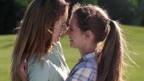 Retrato de las lesbianas sonrientes que abrazan en parque metrajes