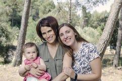 Retrato de las madres felices de las lesbianas con un bebé Fami homosexual Fotos de archivo libres de regalías