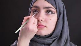 Retrato de las manos femeninas que dibujan la flecha negra usando el cepillo plano fino para la mujer musulmán atractiva en hijab metrajes