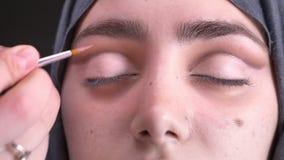 Retrato de las manos femeninas que dibujan la línea rosada usando pequeño cepillo en el ojo derecho para la mujer musulmán hermos metrajes