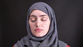 Retrato de las manos femeninas que hacen el maquillaje del ojo que dibuja una línea con el pequeño cepillo para la mujer musulmán almacen de metraje de vídeo