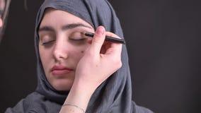 Retrato de las manos femeninas que hacen el maquillaje que dibuja una línea con el lápiz marrón para la mujer musulmán joven en h almacen de metraje de vídeo