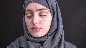 Retrato de las manos femeninas que hacen el stumping del maquillaje del ojo con el cepillo para la mujer musulmán hermosa en hija almacen de metraje de vídeo