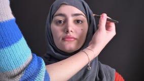 Retrato de las manos femeninas que hacen maquillaje con el lápiz negro para la mujer musulmán joven en hijab en fondo negro almacen de metraje de vídeo