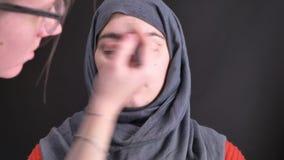 Retrato de las manos femeninas que hacen maquillaje con el lápiz y el cepillo marrones para la mujer musulmán joven en hijab en f almacen de metraje de vídeo