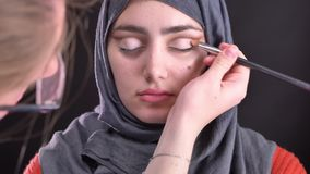 Retrato de las manos femeninas que hacen maquillaje del ojo con el cepillo plano para la mujer musulmán hermosa en hijab en fondo almacen de video