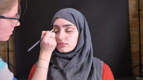 Retrato de las manos femeninas que hacen maquillaje del ojo con el lápiz y el cepillo marrones para la mujer musulmán hermosa en  metrajes