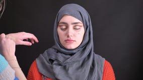 Retrato de las manos femeninas que hacen maquillaje del ojo con el pequeño cepillo para la mujer musulmán hermosa en hijab en fon almacen de metraje de vídeo