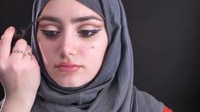 Retrato de las manos femeninas que hacen maquillaje y que cepillan las cejas para la mujer musulmán atractiva en hijab en fondo n metrajes