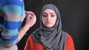 Retrato de las manos femeninas que hacen maquillaje y que ponen en el highlighter en cara de la mujer musulmán atractiva en hijab metrajes