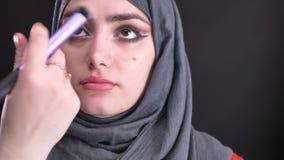Retrato de las manos femeninas que hacen maquillaje y que ponen la fundación para la mujer musulmán atractiva en hijab en negro almacen de metraje de vídeo