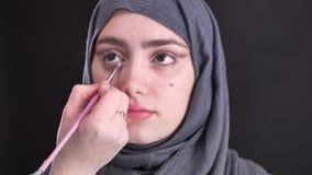 Retrato de las manos femeninas que hacen ojo-maquillaje con el cepillo fino para la mujer musulmán hermosa en hijab en fondo negr almacen de video