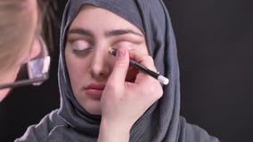 Retrato de las manos femeninas que hacen ojo-maquillaje con el lápiz blanco para la mujer musulmán hermosa en hijab en fondo negr metrajes