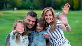 Retrato de las manos que agitan de la familia feliz en el parque almacen de metraje de vídeo