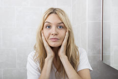 Retrato de las mejillas conmovedoras de la mujer joven en cuarto de baño Imágenes de archivo libres de regalías