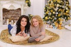 Retrato de las muchachas bonitas que presentan y que sonríen con la tableta en t Foto de archivo libre de regalías