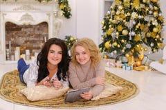 Retrato de las muchachas bonitas que presentan y que sonríen con la tableta en t Imagen de archivo