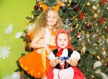 Retrato de las muchachas de los niños en ardillas de un traje alrededor de un árbol de navidad adornado Niños en Año Nuevo del dí Imagen de archivo