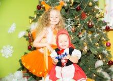 Retrato de las muchachas de los niños en ardillas de un traje alrededor de un árbol de navidad adornado Niños en Año Nuevo del dí Fotografía de archivo