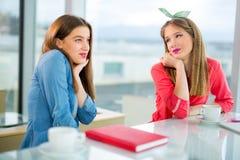 Retrato de las muchachas del adolescente que se sientan en la tabla en el café Fotos de archivo