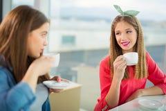 Retrato de las muchachas del adolescente que se sientan en la tabla en el café Fotos de archivo libres de regalías