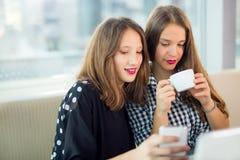Retrato de las muchachas del adolescente que se sientan en la tabla en el café Imagen de archivo libre de regalías