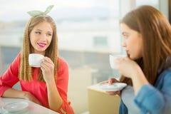 Retrato de las muchachas del adolescente que se sientan en la tabla en el café Imagenes de archivo