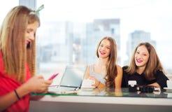 Retrato de las muchachas del adolescente que se sientan en la tabla en el café Imágenes de archivo libres de regalías
