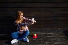 Retrato de las mujeres bonitas jovenes que se fotografían para la imagen social de la red mientras que descansa al aire libre Imagenes de archivo