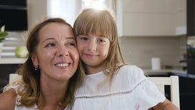 Retrato de las mujeres con la mamá feliz y la hija que sonríen, abrazando, mostrando amor y el afecto adentro dentro en la cocina metrajes