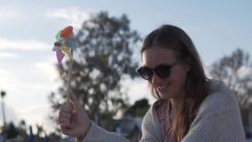 Retrato de las mujeres felices lindas que se divierten con el molinillo de viento almacen de metraje de vídeo
