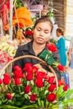 Retrato de las mujeres jovenes del florista del khmer que hacen el ramo de la belleza de rosas rojas en el sendero Mercado de Phs fotografía de archivo
