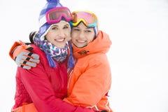Retrato de las mujeres jovenes felices en ropa caliente que abrazan al aire libre Imagenes de archivo