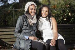 Retrato de las mujeres jovenes que se relajan en banco de parque Foto de archivo libre de regalías