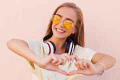 Retrato de las mujeres jovenes sonrientes de la moda de la belleza con las gafas de sol amarillas, auriculares inalámbricos, haci Foto de archivo libre de regalías
