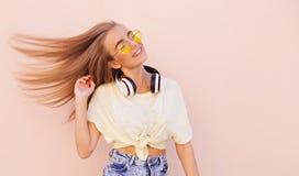 Retrato de las mujeres jovenes sonrientes de la moda de la belleza con las gafas de sol amarillas, los auriculares inalámbricos,  Fotografía de archivo libre de regalías