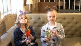 Retrato de las pequeñas muchachas lindas que sostienen los cócteles con la paja, sonriendo HD lleno metrajes