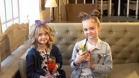Retrato de las pequeñas muchachas lindas que sostienen los cócteles con la paja, sonriendo y hablando el uno al otro el hd comple metrajes